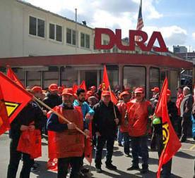Über der Niederlassung des Auto-Zulieferers Dura im Sauerland weht die US-Fahne. Davor rote Fahnen der IG Metall Märkischer Kreis.