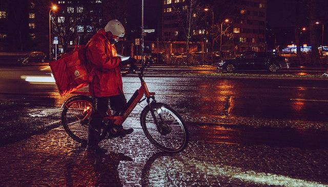 Lieferando-Kurier nachts auf der Straße