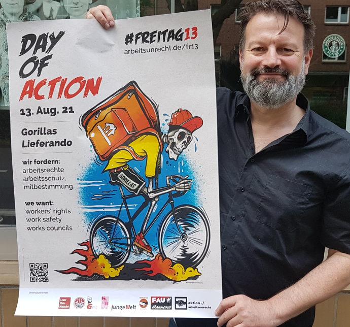 Der Pressesprecher der Aktion gegen Arbeitsunrecht mit dem Plakat zum Aktionstag #Freitag13 Nr. 11 gegen Lieferando & Gorillas.